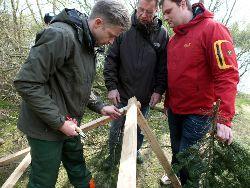 Tannenzweige werden an eine Holzkonstruktion geflochten.